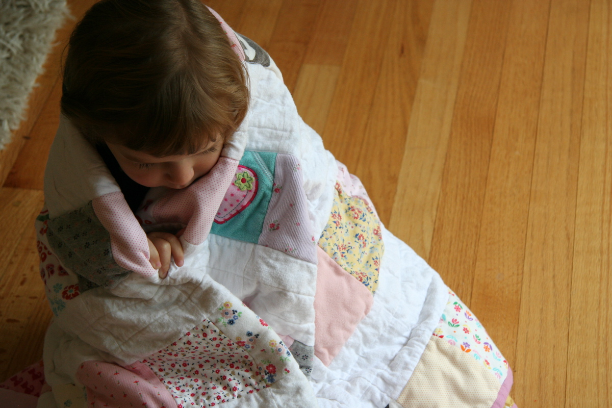 Phoebe wrapped in her baby clothes quilt